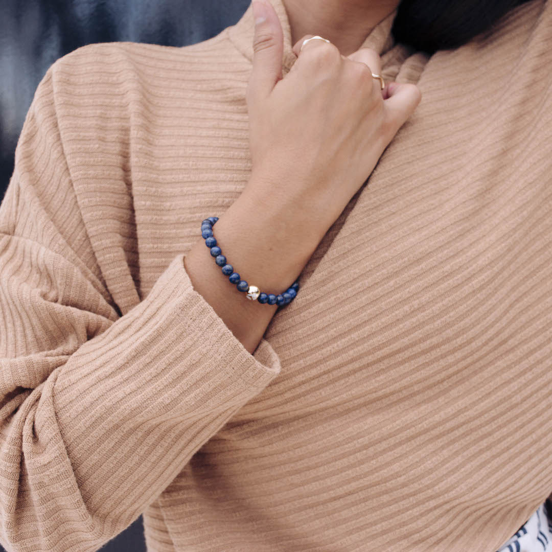 Female in tan turtle neck sweater holding collar with deep blue stone bracelet on wrist.
