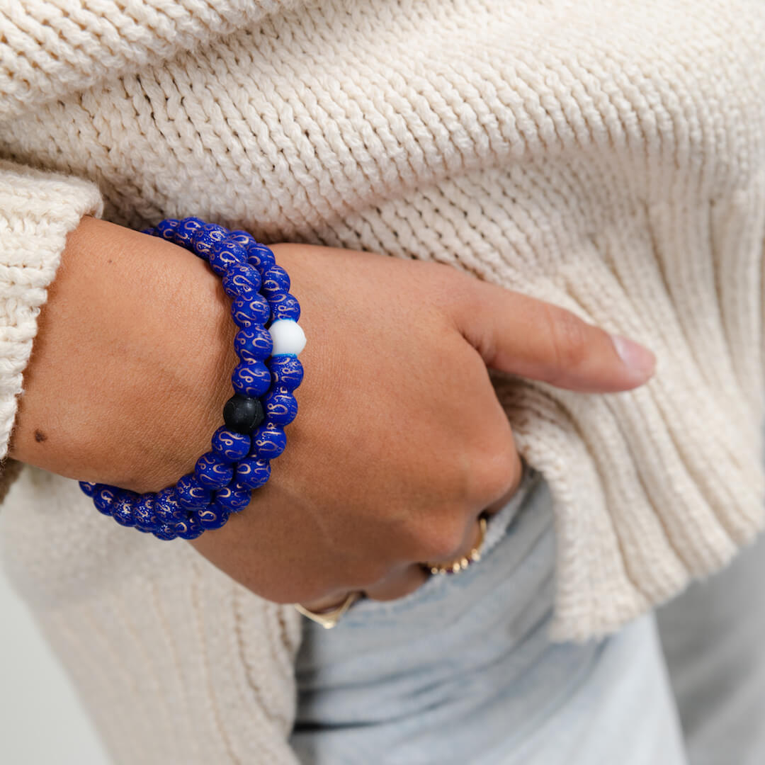Girl wearing a silicone beaded bracelet with Leo symbol pattern on wrist.