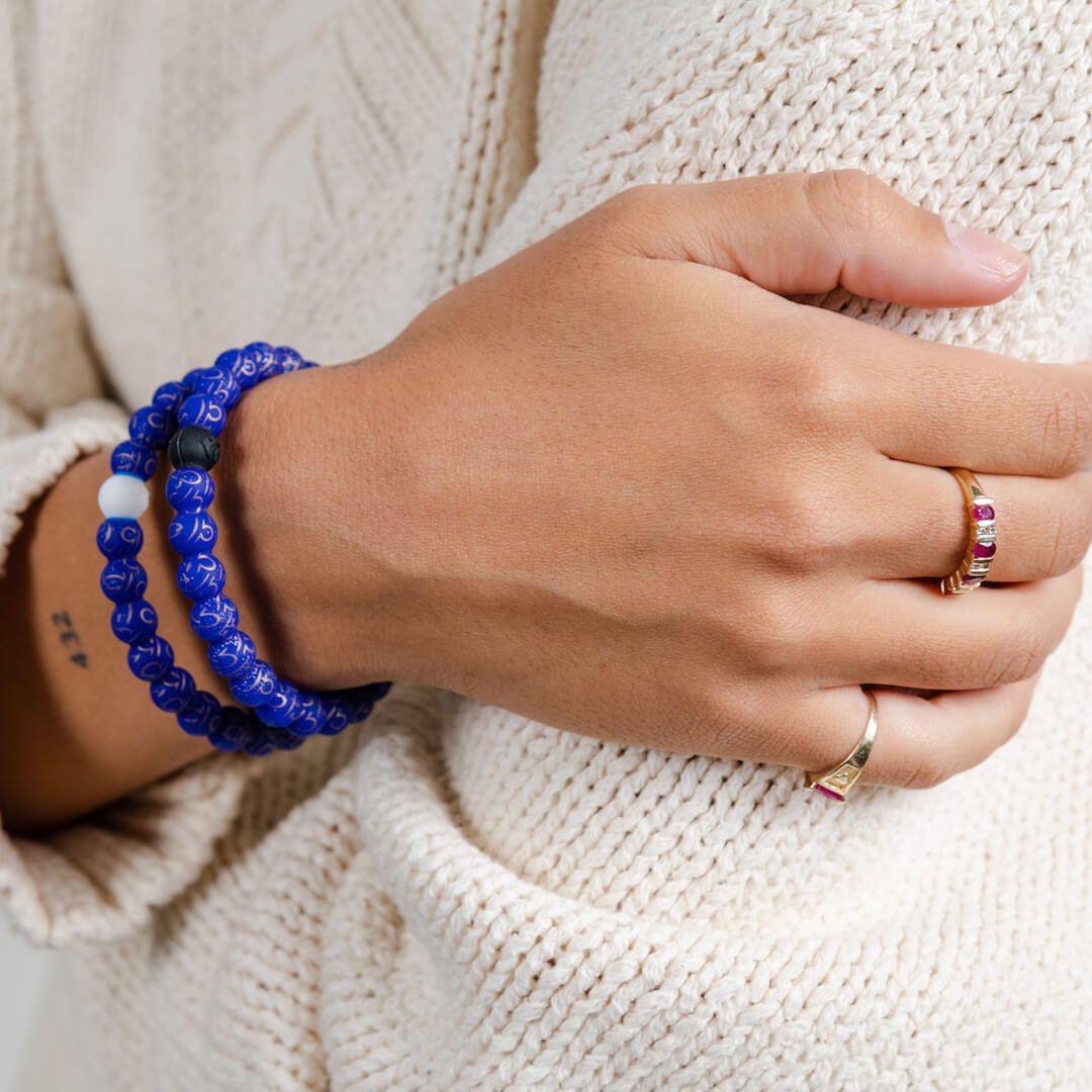 Girl wearing a silicone beaded bracelet with Libra symbol pattern on wrist.