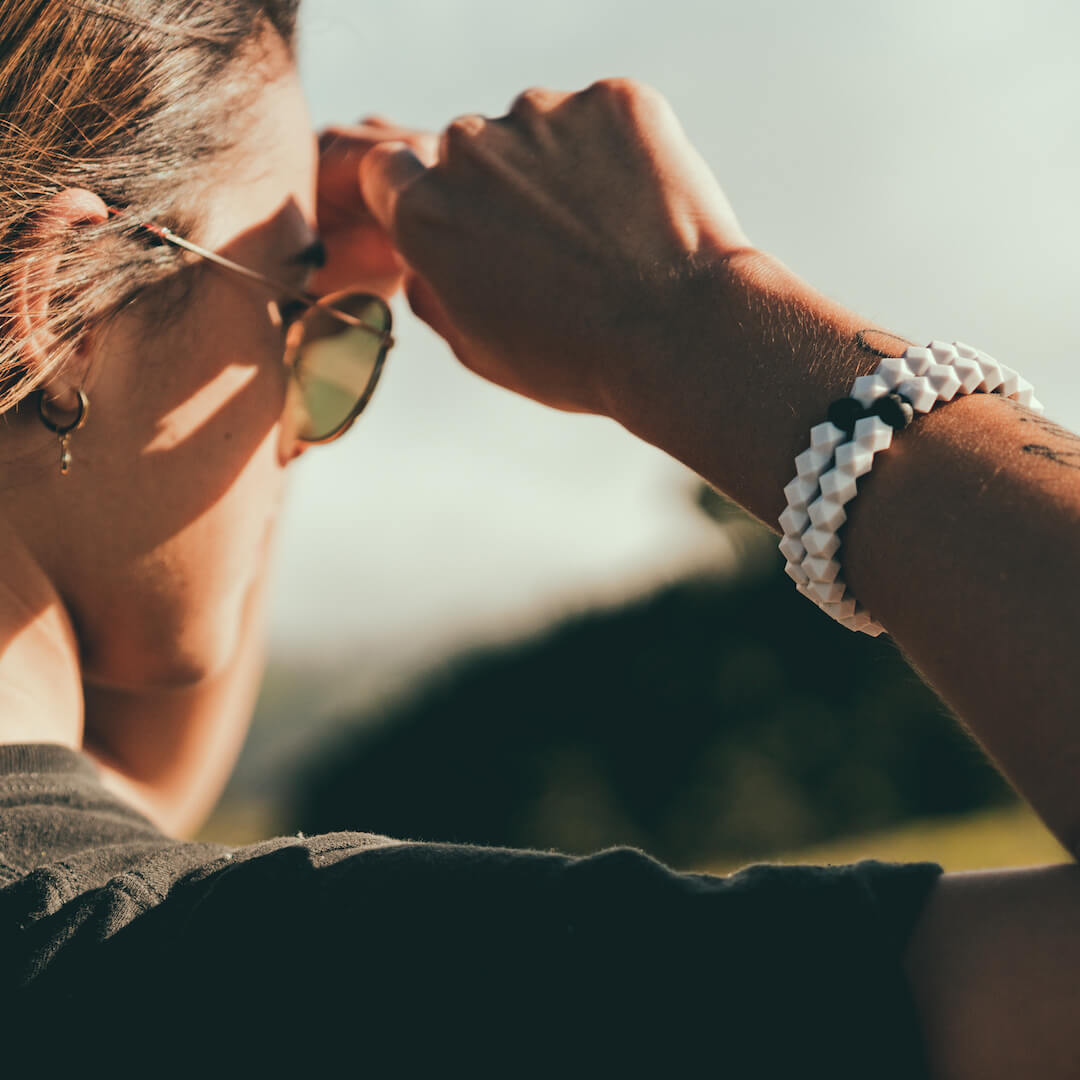 Female wearing silicone hexagon shaped beaded bracelet on wrist while blocking sun from her eyes