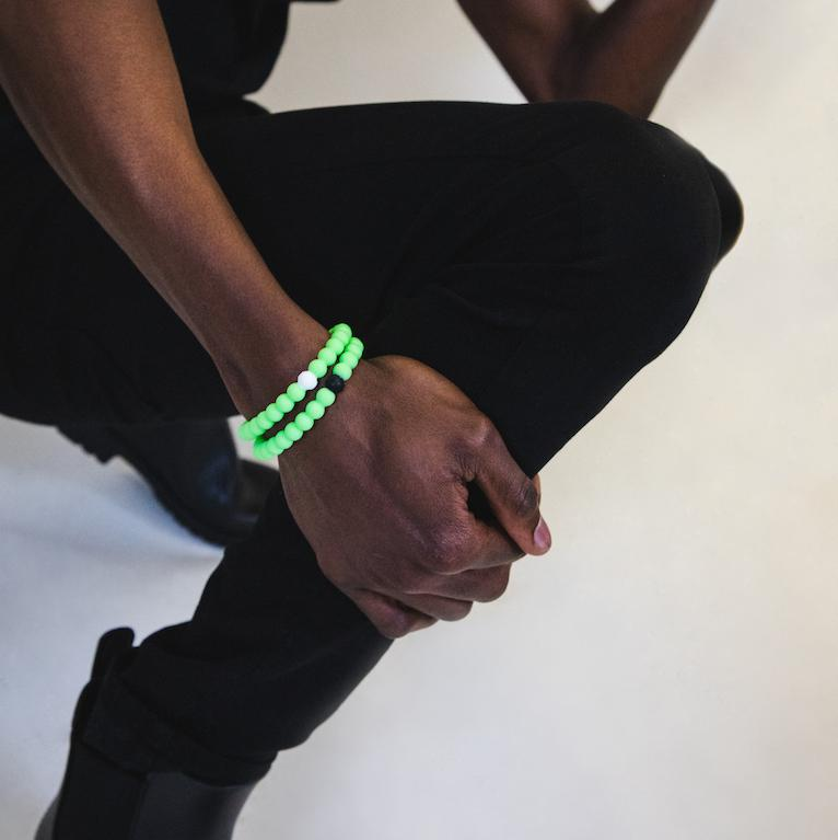 Male wearing all black with two neon green silicone beaded bracelets on wrist while holding his leg.