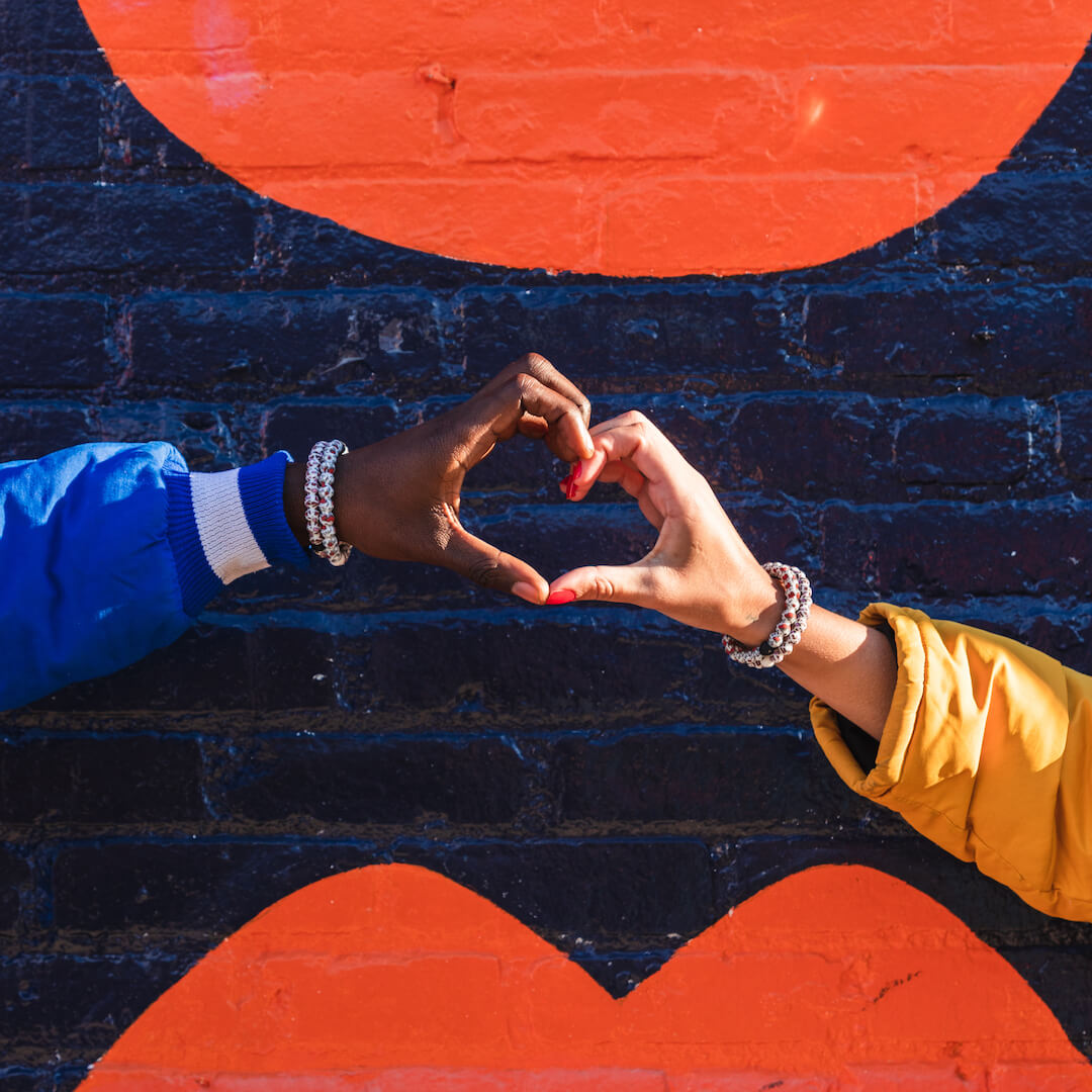 Two people making a heart with their hands both wearing silicone beaded bracelet with Keith Haring Heart pattern on wrist.