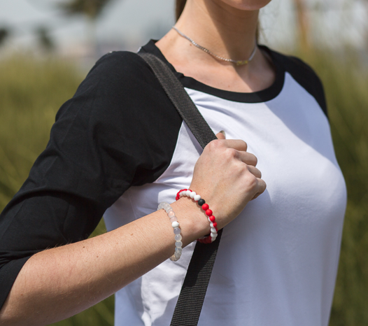 Female wearing red and white silicone beaded bracelet on wrist while holding shoulder bag straps.