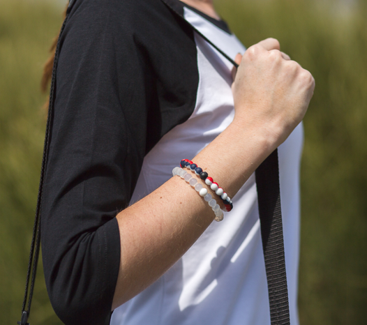 Woman wearing red, white and navy blue silicone beaded bracelet on wrist while holding shoulder bag strap.