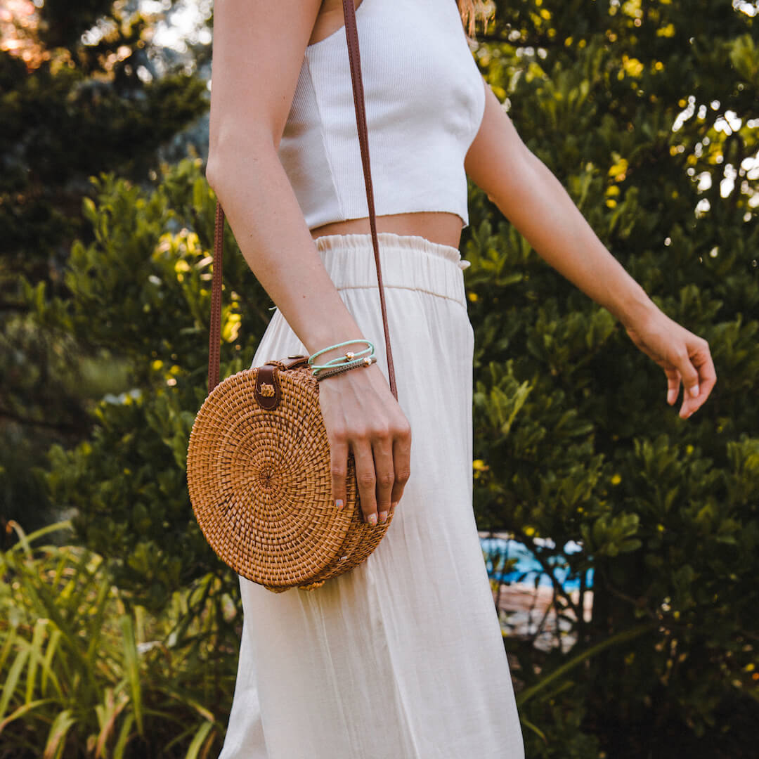 Female in all white outfit wearing mint triple wrap woven bracelet on wrist while resting hand on woven purse.