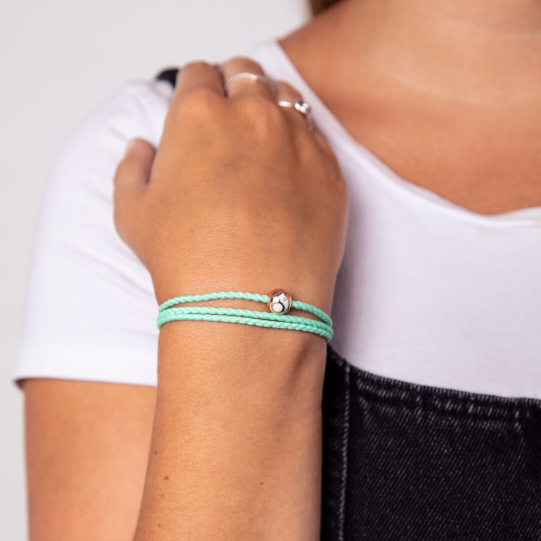 Female wearing mint triple wrap woven bracelet while touching her shoulder.