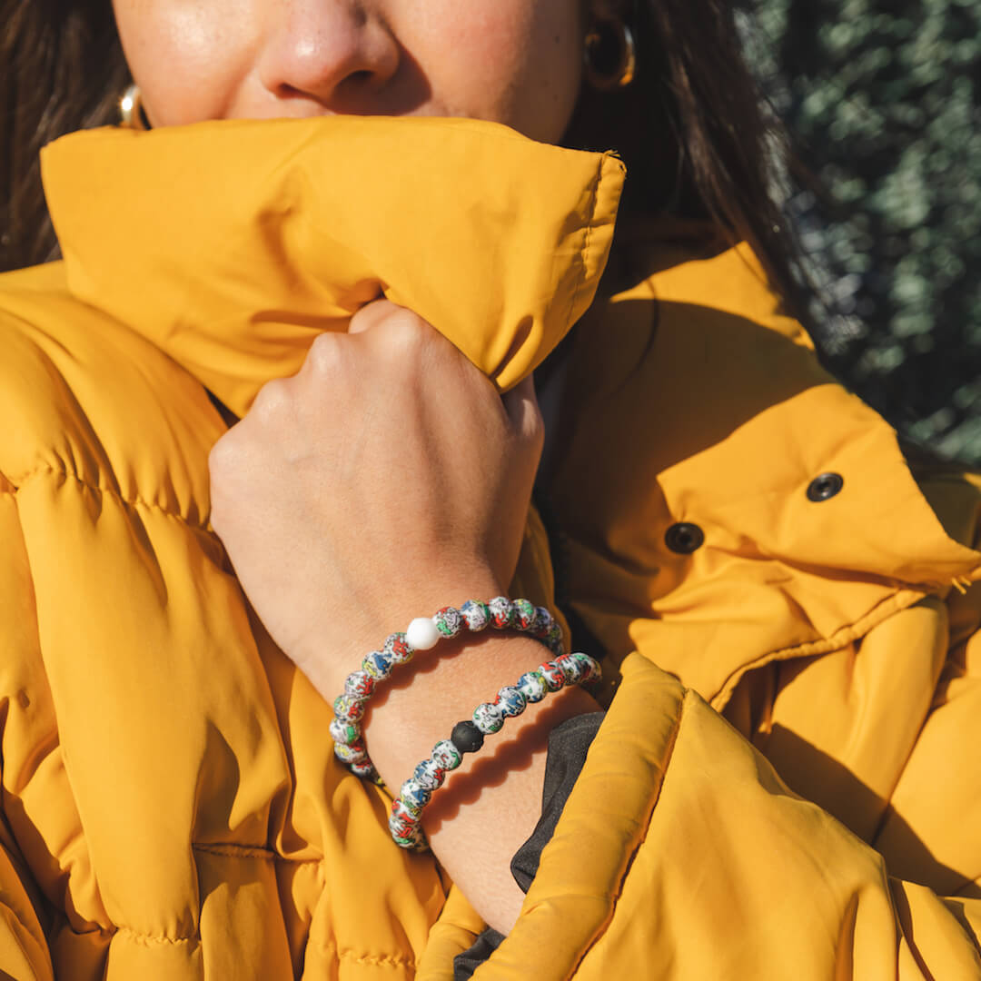 Girl in yellow jacket wearing two silicone beaded bracelets with Keith Haring character pattern on wrist.