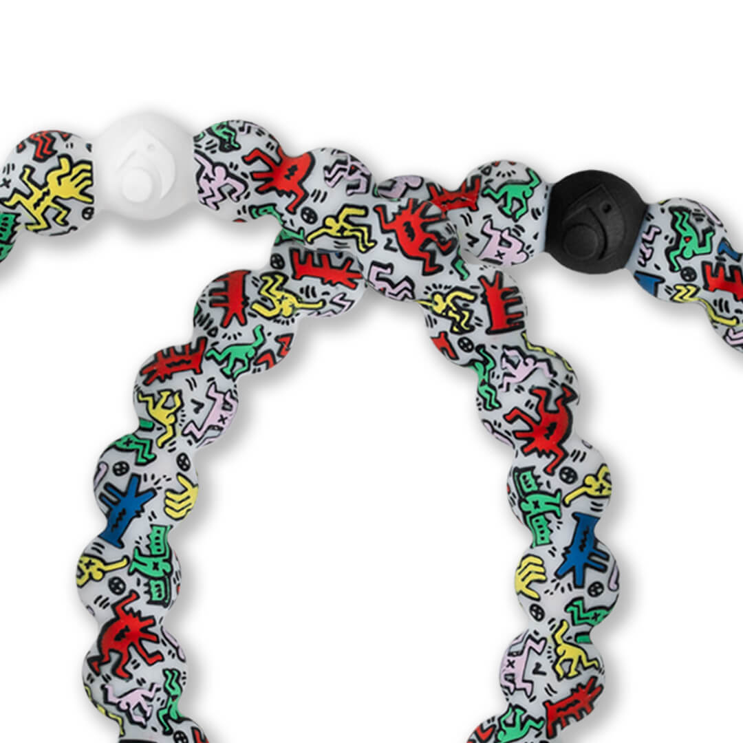 Close up of a silicone beaded bracelet with Keith Haring character pattern.