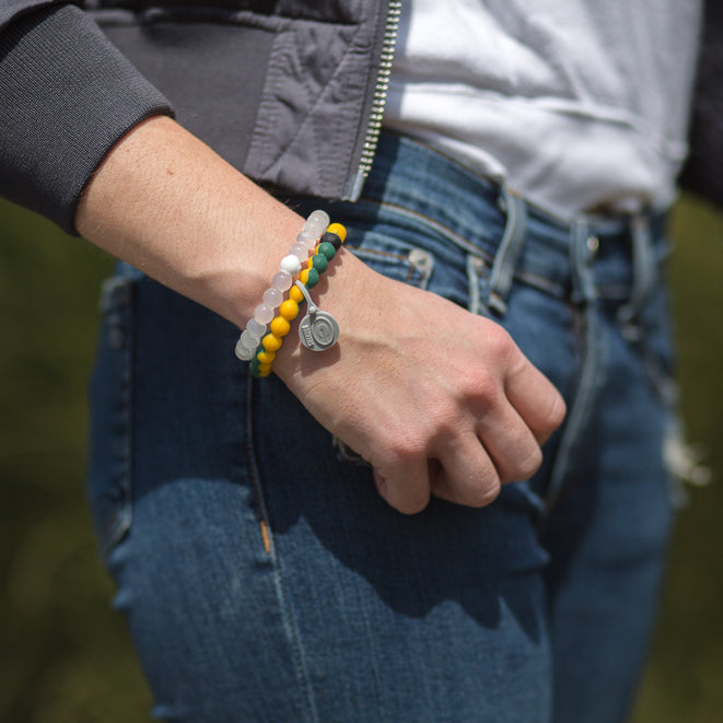 Woman with hand in pocket wearing a green and yellow swirl silicone beaded bracelet on wrist