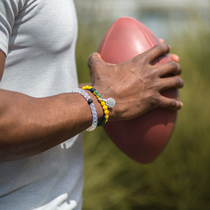 Male holding a football wearing a green and yellow swirl silicone beaded bracelet