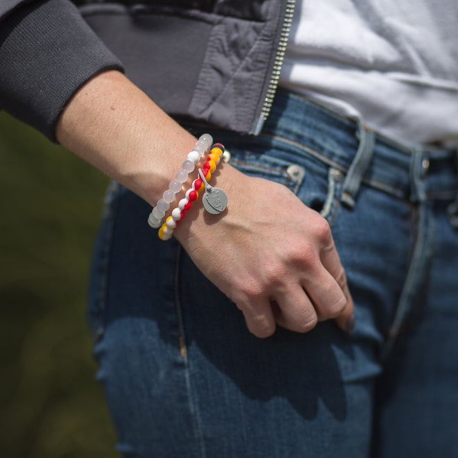 Woman wearing a red, yellow and white swirls silicone beaded bracelet on wrist