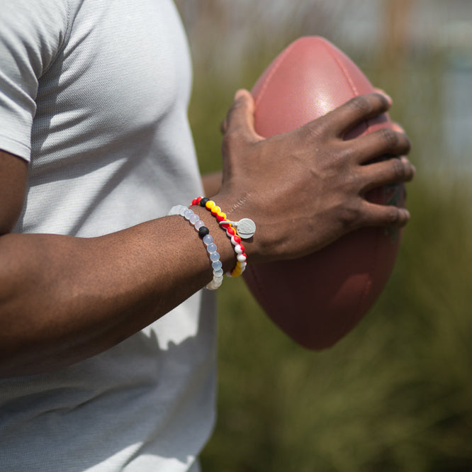 Male holding football wearing a red, yellow and white swirls silicone beaded bracelet