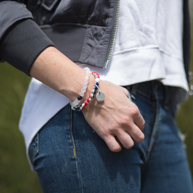 Woman with hand in pocket wearing a red, white, blue and gray swirl silicone beaded bracelet.