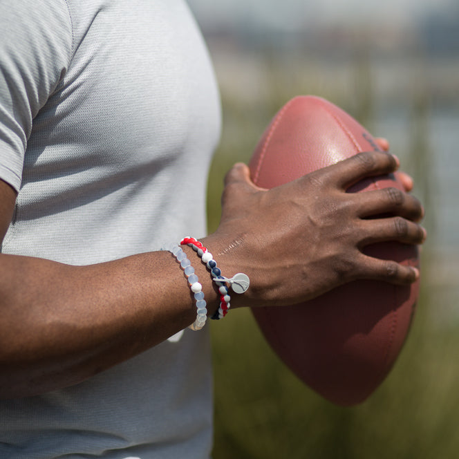 Male holding football wearing a red, white, blue and gray swirl silicone beaded bracelet.