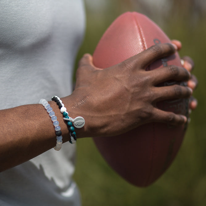 Male holding football with black, white and teal silicone beaded bracelet on wrist.