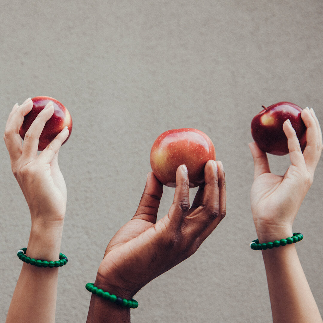 Three hands holding red apples in the air with hunter green silicone beaded bracelets on wrist.
