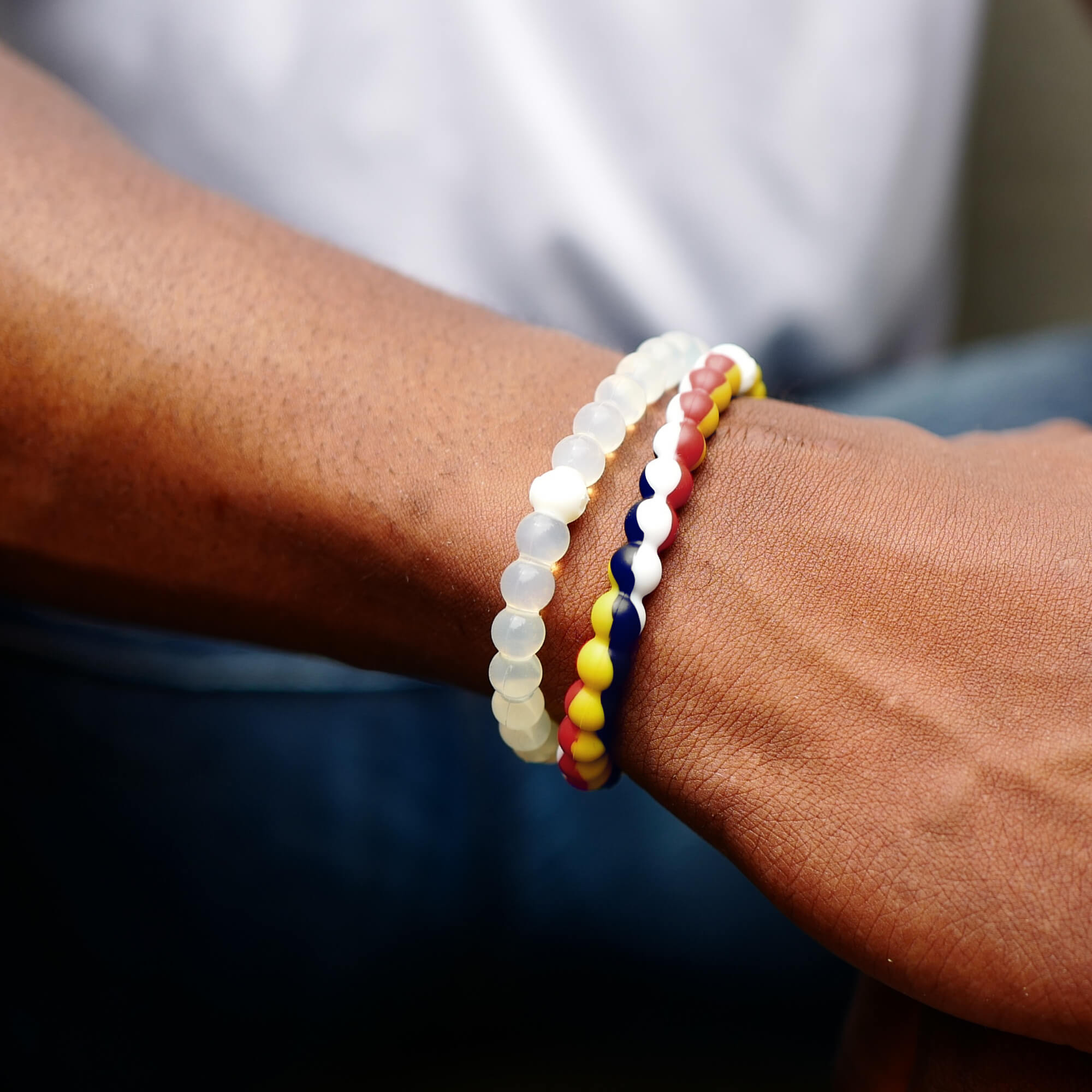 A hand wearing a red, yellow, white and navy silicone beaded bracelet.
