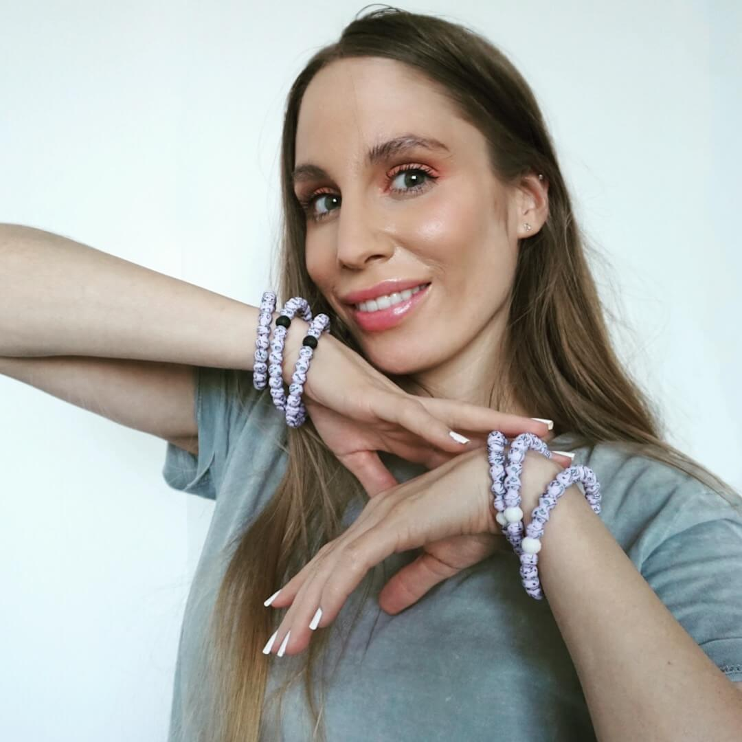 Woman wearing light purple silicone beaded bracelet with workout equipment icons on wrist.