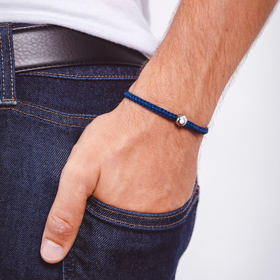 Male wearing navy blue woven bracelet with silver metal bead on wrist with his hand in his back pocket.