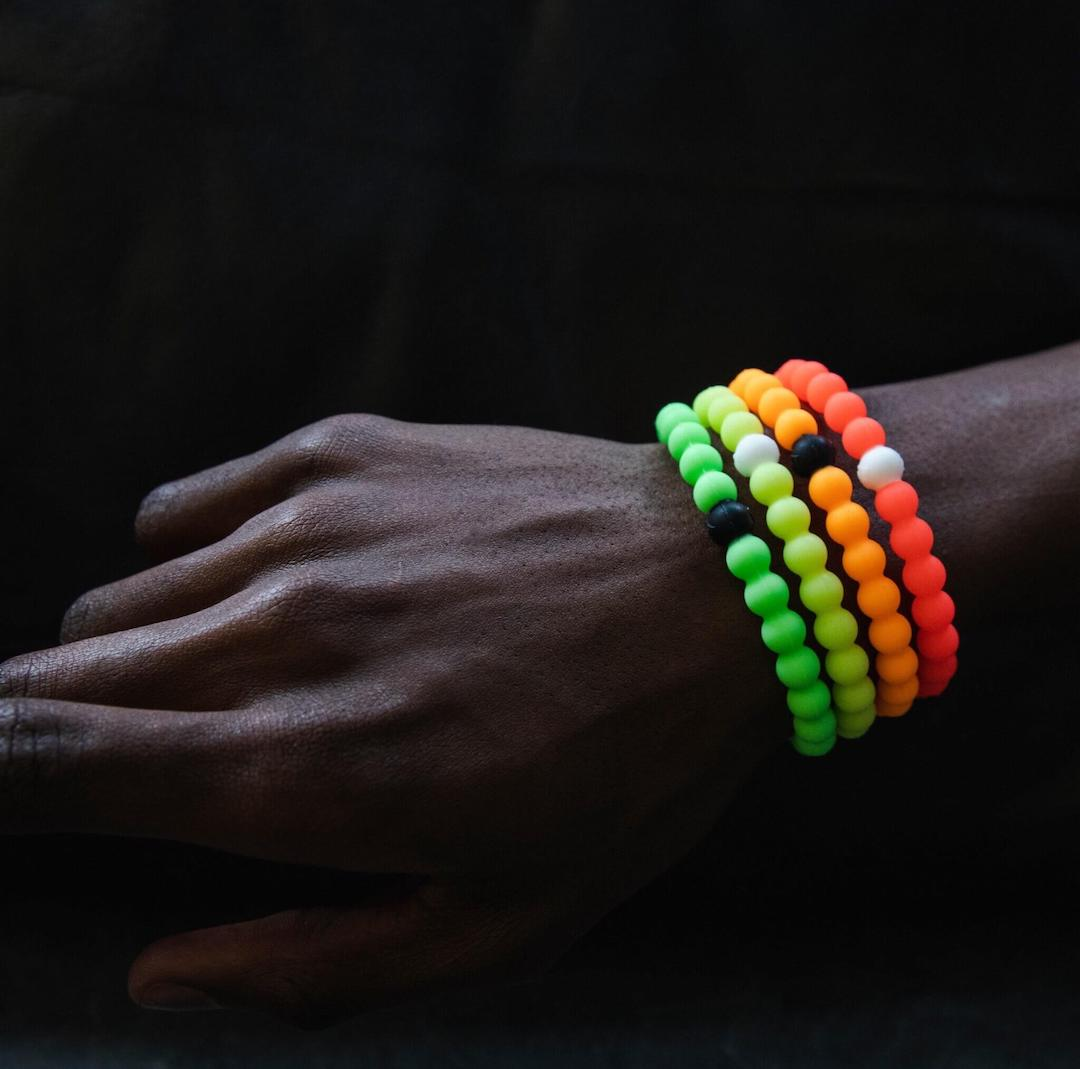 Male wearing stack of neon green, yellow, orange and pink silicone beaded bracelets on wrist with a black background.