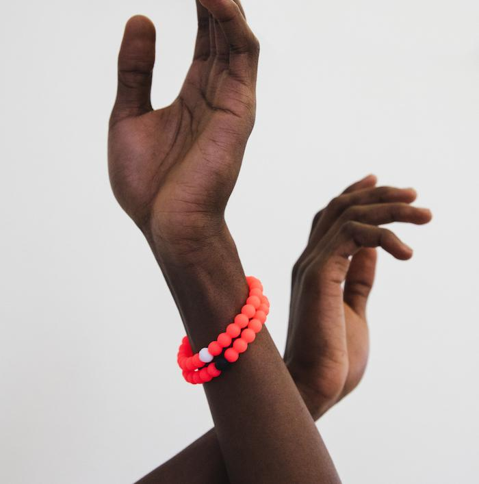 Male wearing two neon pink silicone beaded bracelets on wrist with arms crossed in the air.