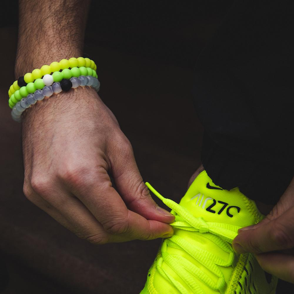 Male tying neon yellow shoes wearing stack of clear, neon green and neon yellow silicone beaded bracelets on wrist.