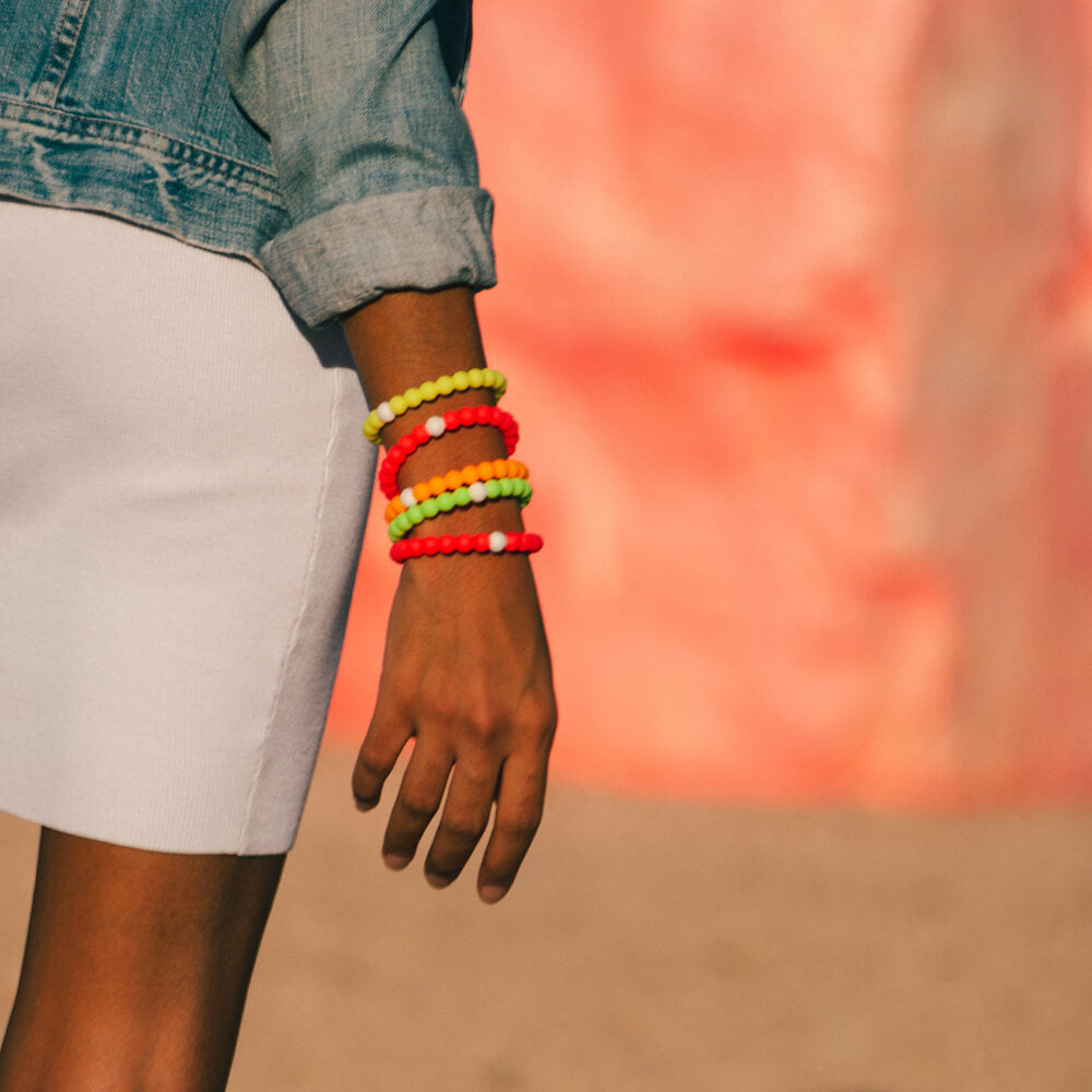 Female wearing a skirt and denim jacket with stack of neon pink, green, orange and yellow silicone beaded bracelets on wrist.