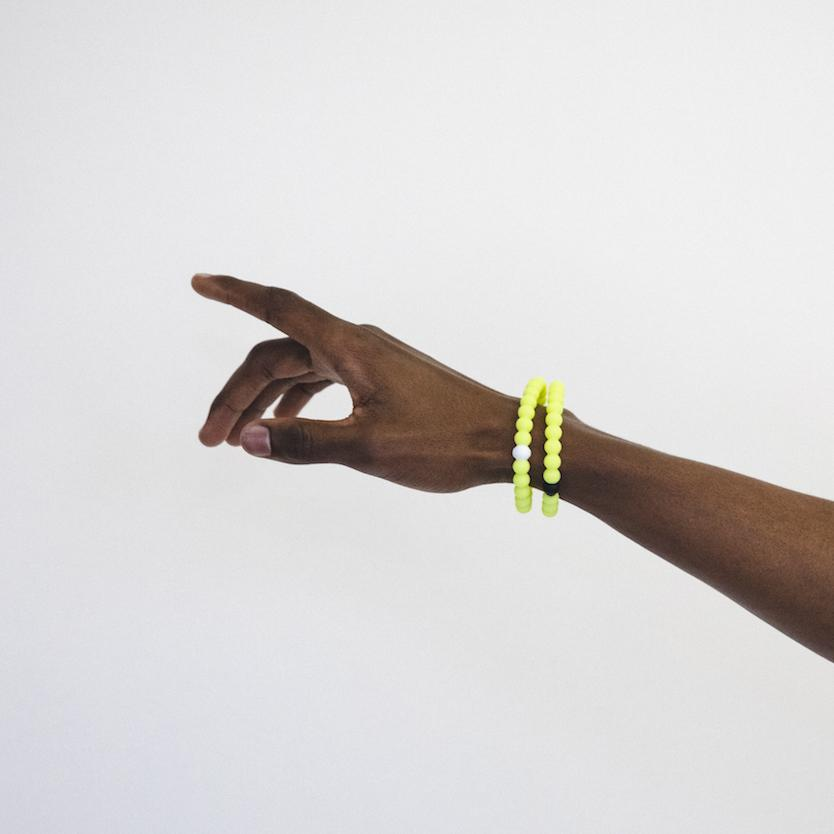 Male arm pointing left wearing two neon yellow silicone beaded bracelets.