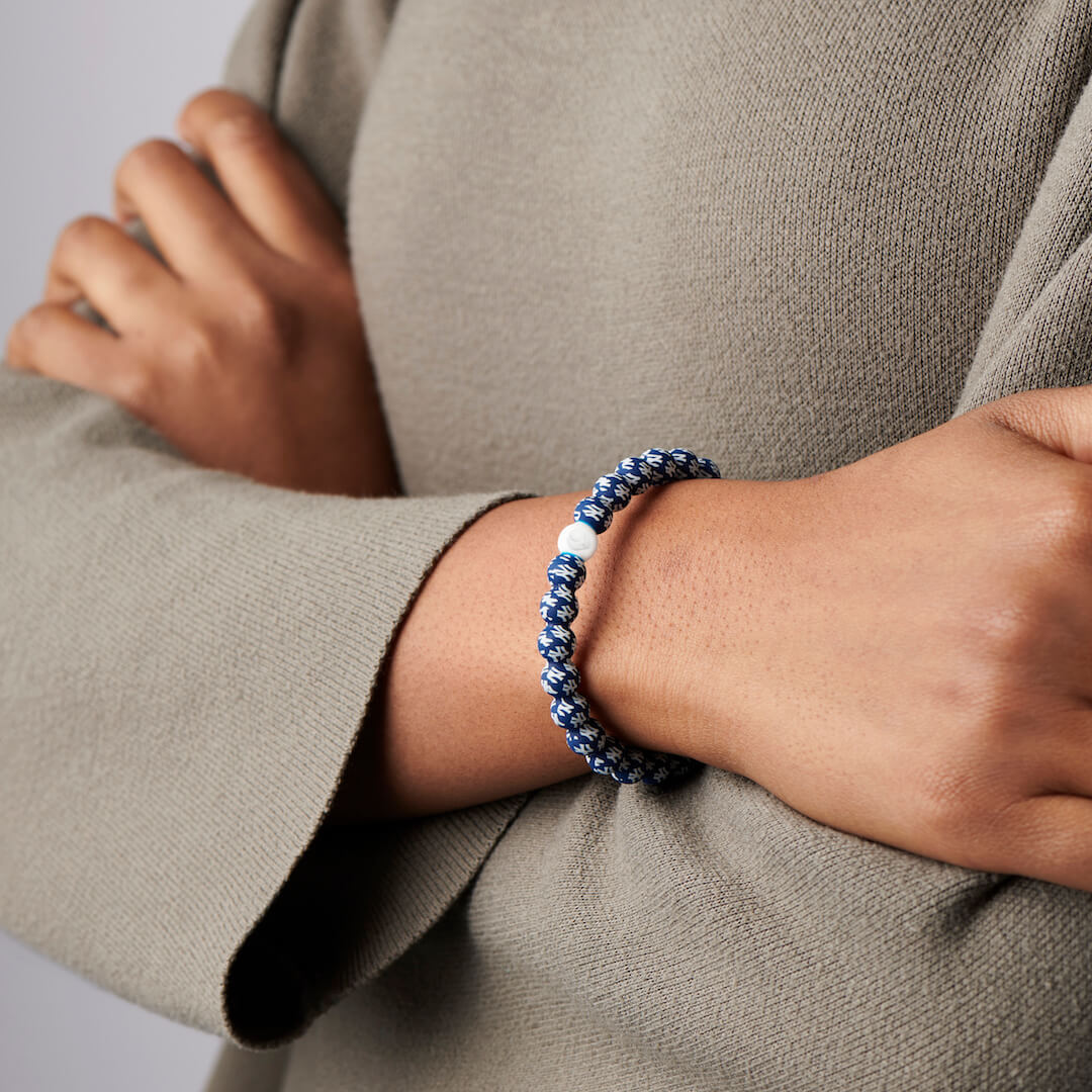 Person wearing a silicone beaded bracelet with New York Yankees Logo pattern.