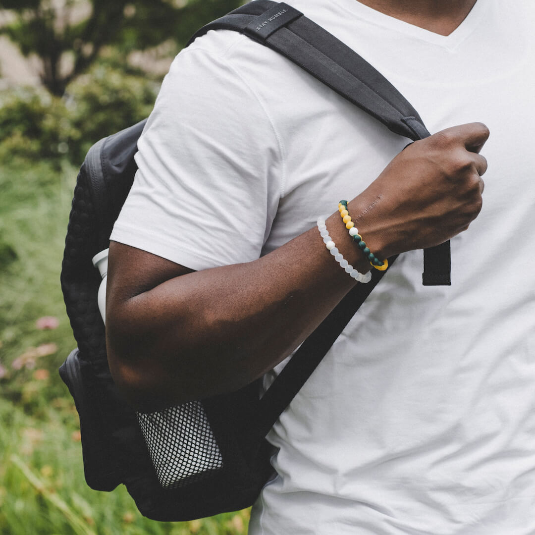 Man holding backpack strap wearing a dark green and yellow silicone beaded bracelet.