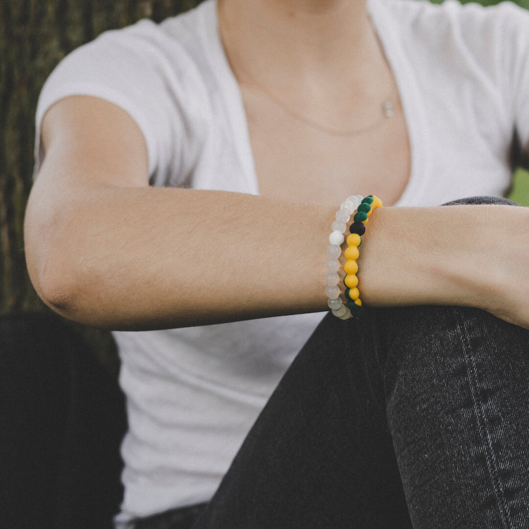 Close-up of woman wearing dark green and yellow silicone beaded bracelet.