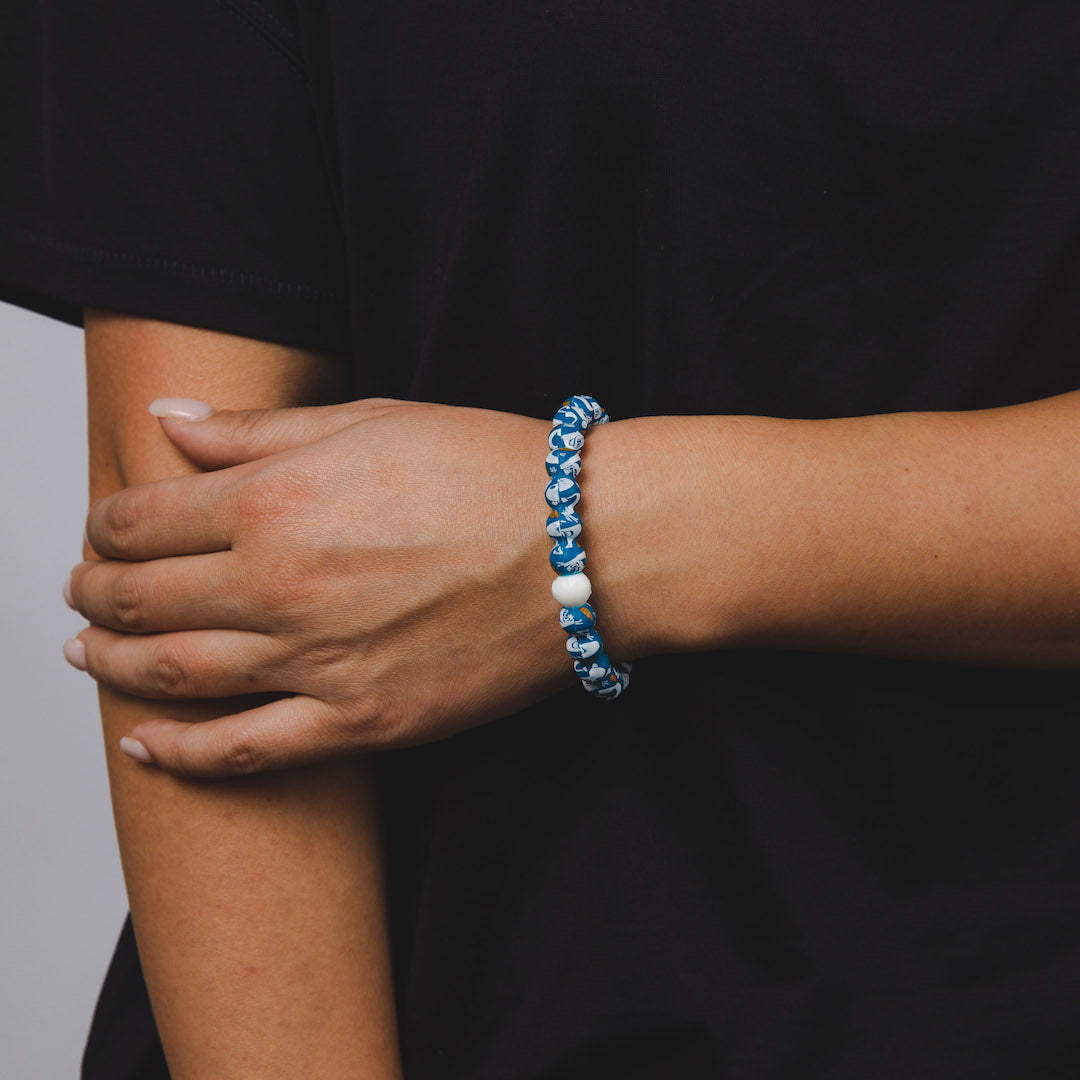 Woman wearing silicone beaded bracelet with Olaf pattern on wrist