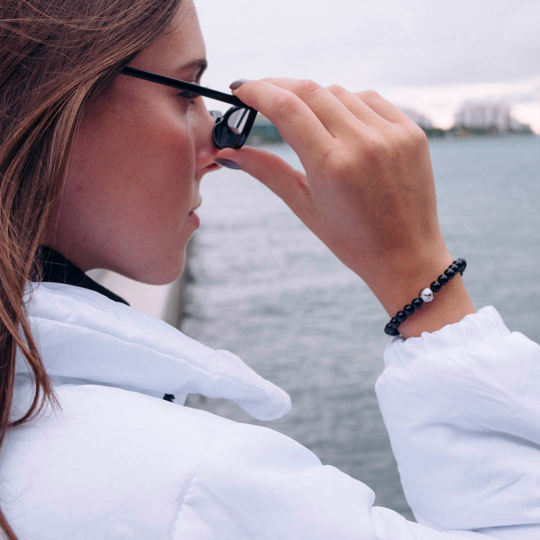 Woman wearing white jacket with black stone bracelet on wrist while touching her sunglasses.
