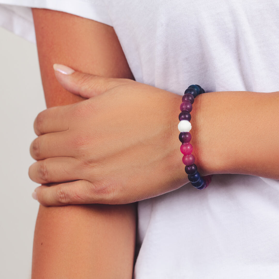 Female wearing galaxy patterned silicone beaded bracelet on wrist while holding her other arm.
