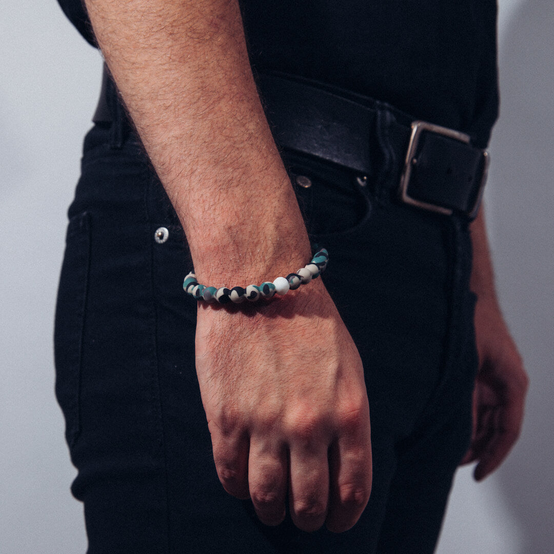 Male wearing camouflage patterned silicone beaded bracelet with hand hanging by his side.