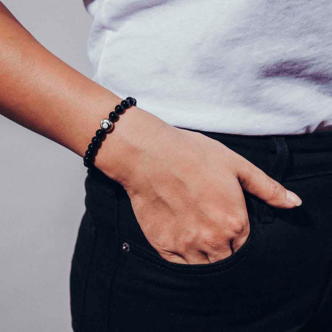 Female wearing black stone bracelet on wrist with hand in pocket.