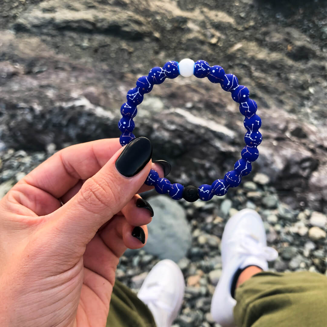 Person holding  a silicone beaded bracelet with Constellation symbol pattern.