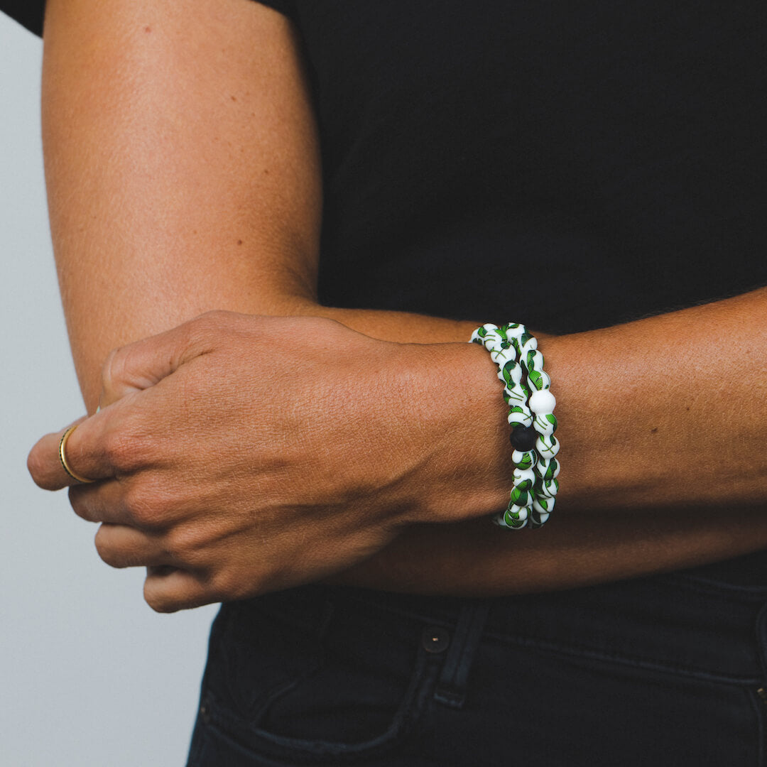 Female wearing two banana leaf patterned silicone beaded bracelets on wrist with arms folded.
