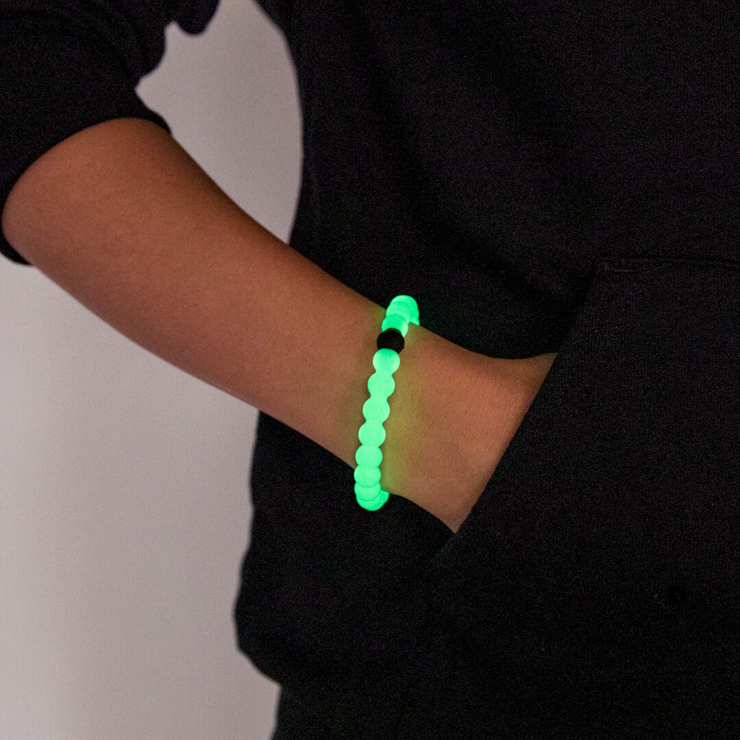 Female in black sweater with hand in pocket wearing a glow in the dark silicone beaded bracelet.