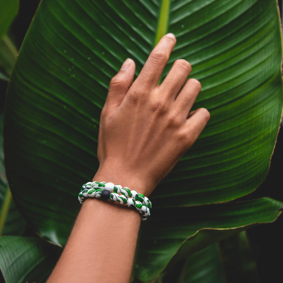 Hand on large banana leaf with two banana leaf patterned silicone beaded bracelets on wrist.