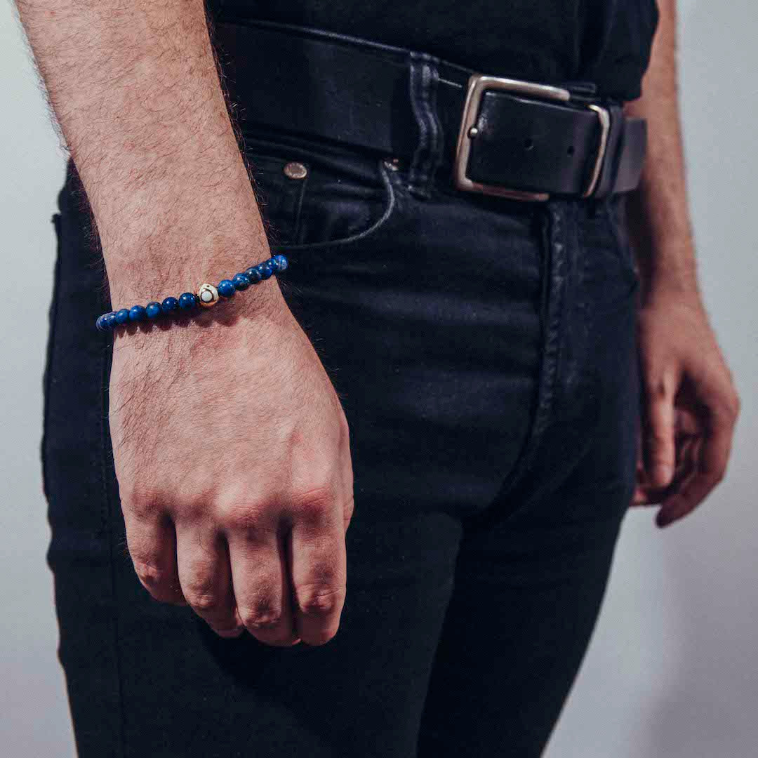 Deep blue stone bracelet on male wrist with hand hanging by his side.