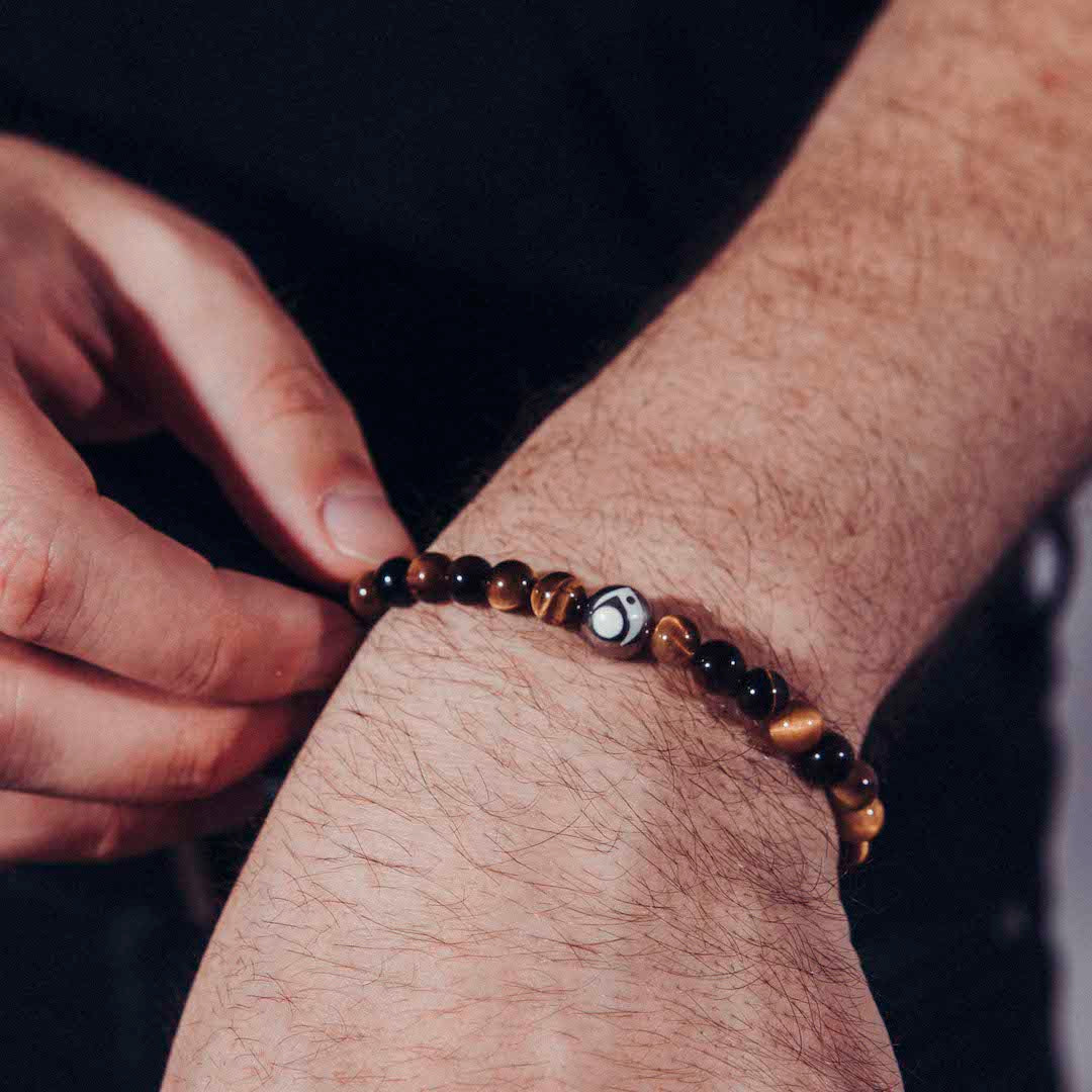 Close up of male adjusting brown stone bracelet on wrist.