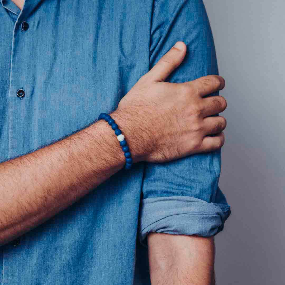 Male in blue denim shirt wearing a classic blue silicone beaded bracelet on wrist while holding his arm.