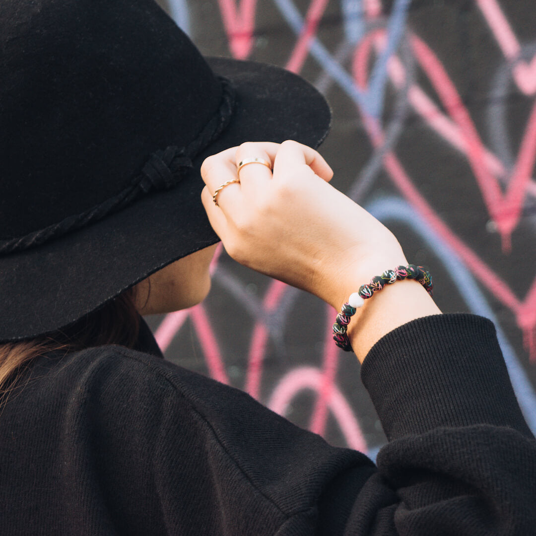 Woman wearing all black with black silicone beaded bracelet with rainbow hearts on wrist while touching her hat.