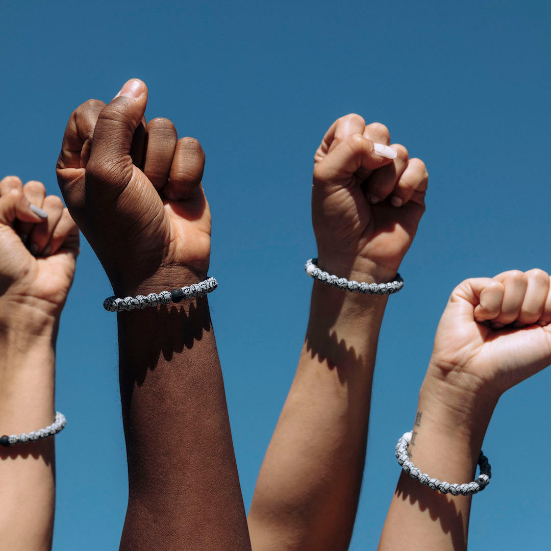 People wearing black lives matter silicone beaded bracelets on wrist with fists in the air.