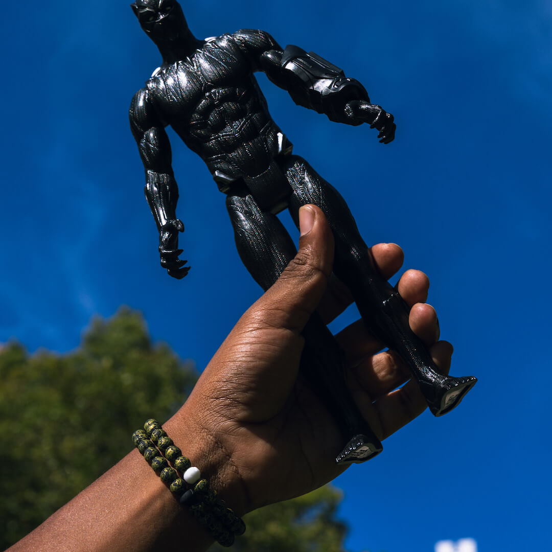 Man holding a Black Panther action figure wearing a silicone beaded bracelet with black and gold Black Panther pattern.