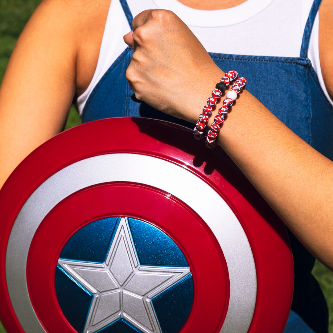 Woman holding Captain America's shield wearing a silicone beaded bracelet with Captain America's shield pattern on wrist.