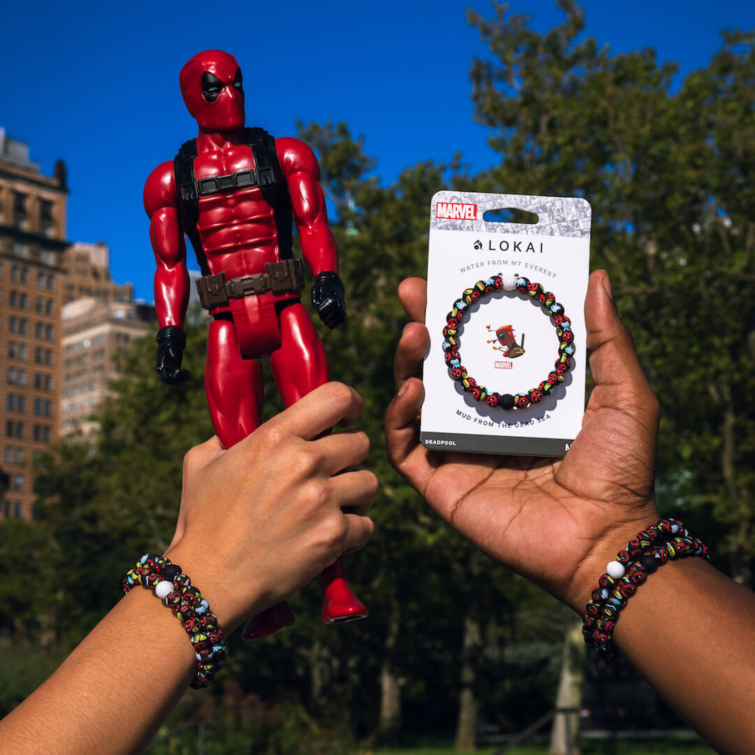 People holding a Deadpool action figure wearing silicone beaded bracelet with Deadpool pattern on wrist.