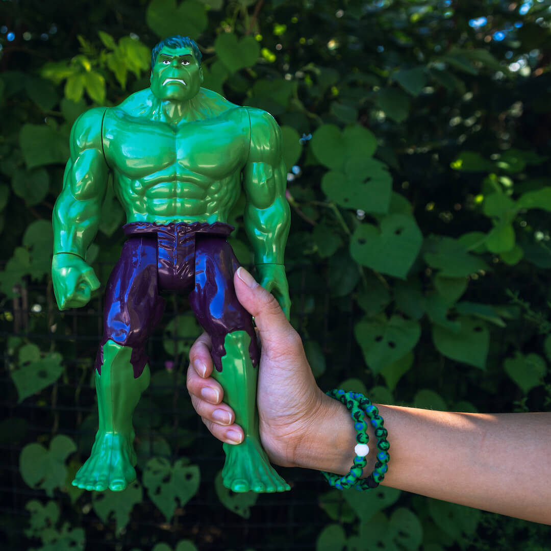 Woman holding a Hulk action figure wearing two silicone beaded bracelets with Hulk fist pattern on wrist.