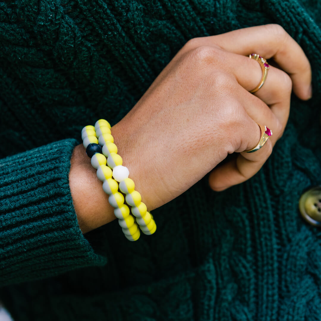 Girl wearing two yellow and gray split silicone beaded bracelets on wrist.